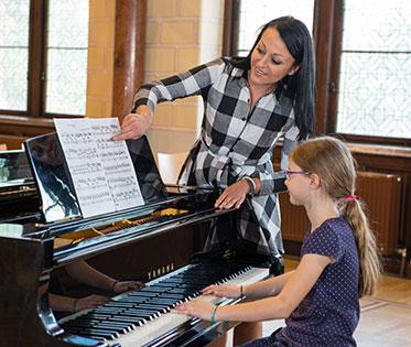 Mädchen erhält Klavierunterricht