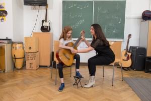Mädchen lernt mit Lehrkraft Gitarre spielen