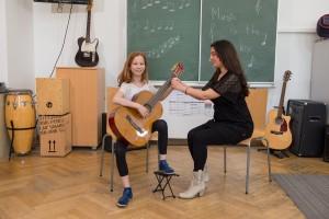 Mädchen lernt Gitarre spielen
