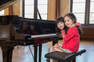 Zwei Mädchen sitzend vor dem Klavier
