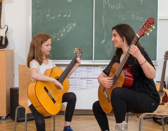 Frau zeigt Mädchen Gitarrengriff