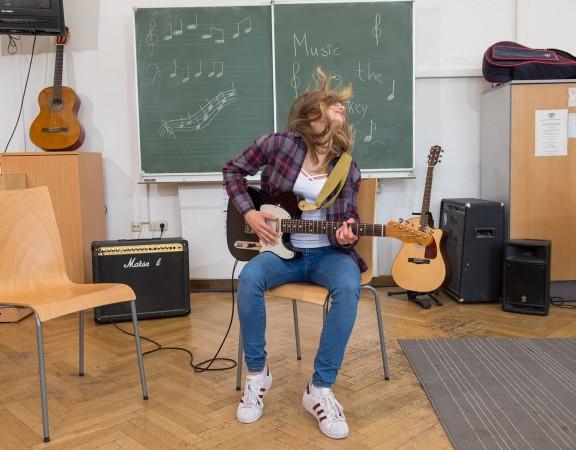 Mädchen rockt auf Gitarre: E-Gitarre lernen für Kinder und Jugendliche