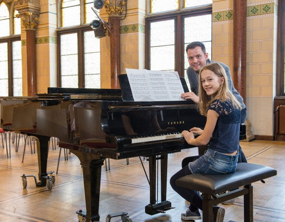 Ein Mann gibt Mädchen Klavierunterricht in Wien