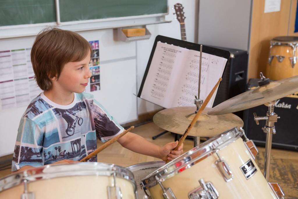 Junge hält Drum Sticks eines Schlagzeugs